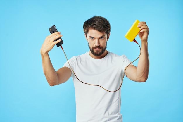 Przystojny samiec model z brodą z telefonem pozuje w studiu