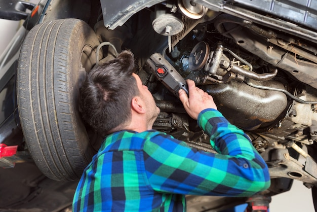 Przystojny samochodowy mechanik sprawdza zawieszenie system zniesiony samochód przy remontową stacją obsługi.