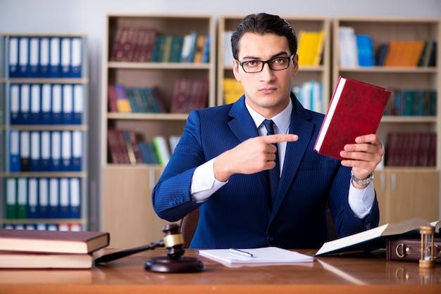 Przystojny sędzia z młotek siedzi w sali sądowej