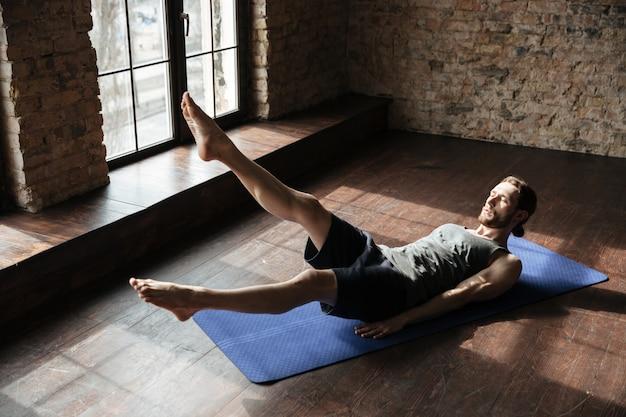 Przystojny silny sportowiec w siłowni robi ćwiczenia jogi