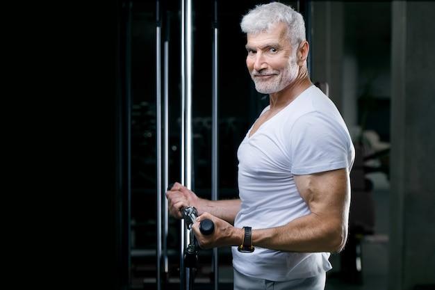 Przystojny Siwy Starszy Mężczyzna Na Siłowni Maszynowej. Koncepcja Sportu I Opieki Zdrowotnej Premium Zdjęcia