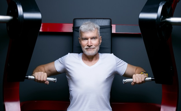 Przystojny siwy starszy mężczyzna na siłowni maszynowej. koncepcja sportu i opieki zdrowotnej