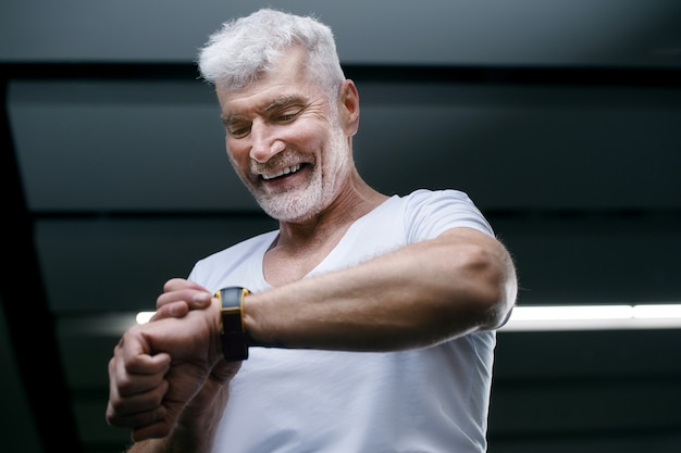 Przystojny siwy starszy mężczyzna patrząc na zegarek sportowy w ręku. koncepcja sportu i opieki zdrowotnej