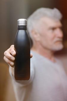Przystojny siwy starszy mężczyzna w białej koszuli z butelką wody. koncepcja sportu i opieki zdrowotnej