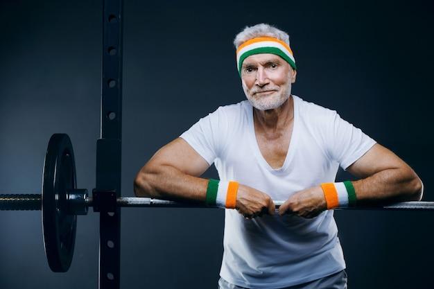 Przystojny siwy starszy mężczyzna z opaską na głowie i opaskami koncepcja sportu i opieki zdrowotnej