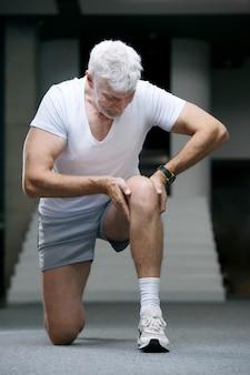 Przystojny siwy starszy mężczyzna zranił kolano lub nogę koncepcja sportu i opieki zdrowotnej