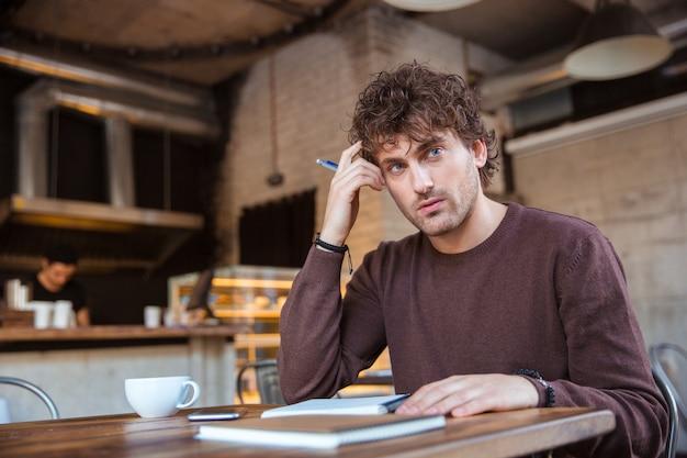 Przystojny, skoncentrowany, atrakcyjny, kędzierzawy młody mężczyzna pisze notatki w notatniku i planuje swój harmonogram, siedząc w kawiarni przy drewnianym stole