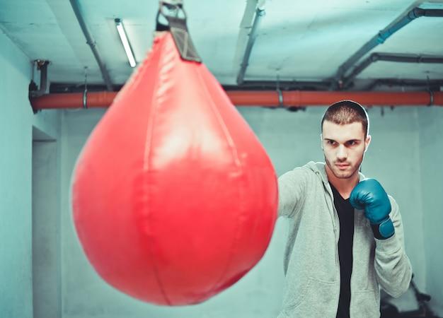 Przystojny skoncentrowany męski bokser trenuje ciosy ręczne z workiem treningowym.
