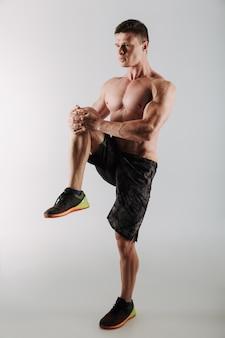 Przystojny skoncentrowany młody sportowiec wykonuje ćwiczenia rozciągające