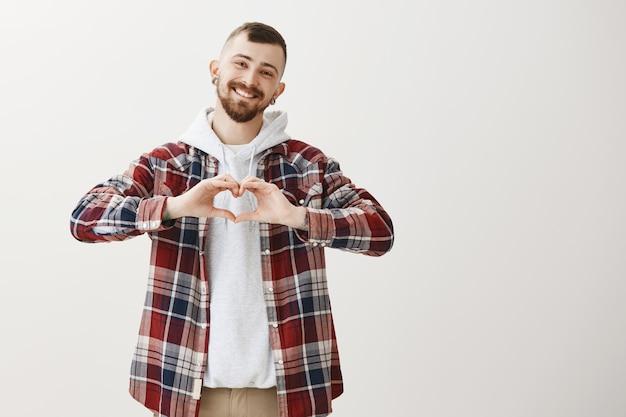 Przystojny śliczny chłopak pokazuje gest serca i uśmiechnięty ładny