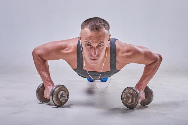Przystojny sportowiec jest wyciskany z podłogi z hantlami w rękach