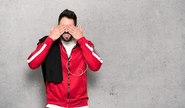 Przystojny sportowiec obejmujących oczy rękoma. zaskoczony, widząc, co jest przed teksturowaną ścianą