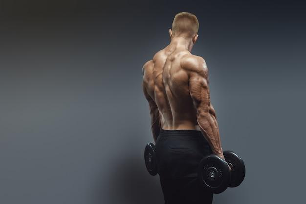 Przystojny sportowiec trening bicepsów z hantlami. muskularny mężczyzna model kulturysta robi ćwiczenia z hantlami, odwrócony. silne, umięśnione plecy męskiego kulturysty.