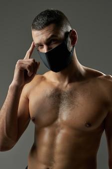 Przystojny sportowiec w masce ochronnej trzymający rękę w pobliżu głowy w pomieszczeniu
