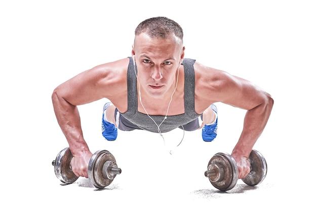 Przystojny sportowy mężczyzna wykręcający się z podłogi z hantlami w dłoniach na białym tle