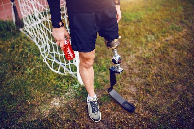 Przystojny, sportowy, niepełnosprawny mężczyzna w odzieży sportowej ze sztuczną nogą, stojąc na boisku piłkarskim i trzymając napoje.