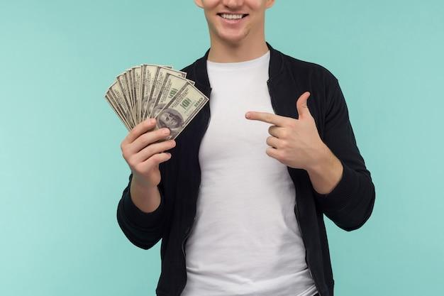 Przystojny sportowy rudowłosy facet wskazując palcem pieniądze na niebieskim tle. - wizerunek