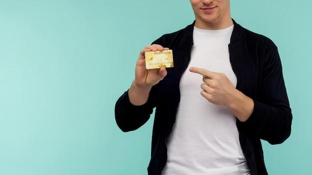 Przystojny sportowy rudowłosy facet wskazując palcem złota karta kredytowa na niebieskim tle. - wizerunek