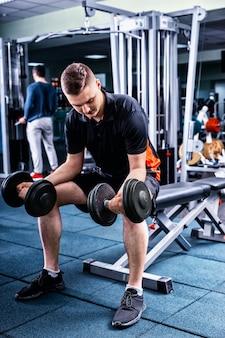 Przystojny sprawny mężczyzna w sportowej, podnosząc ciężary i pracujący na bicepsach w siłowni