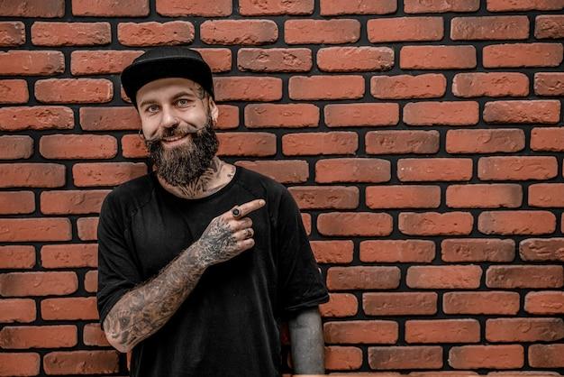 Przystojny staromodny hipster w koszulce i czapce, pozie i uśmiechu. na tle cegły.