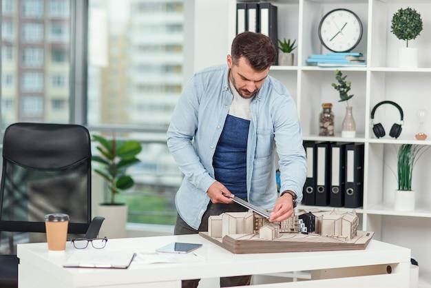 Przystojny starszy architekt kaukaski pracujący nad projektem budowlanym i badający model, na którym pracuje.