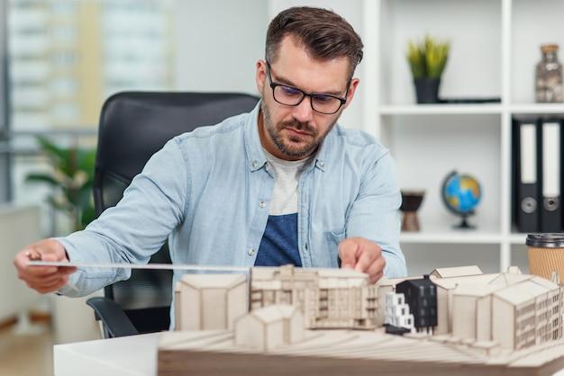 Przystojny starszy architekt kaukaski przy okularach pracuje nad projektem budowlanym i bada model, nad którym pracuje.