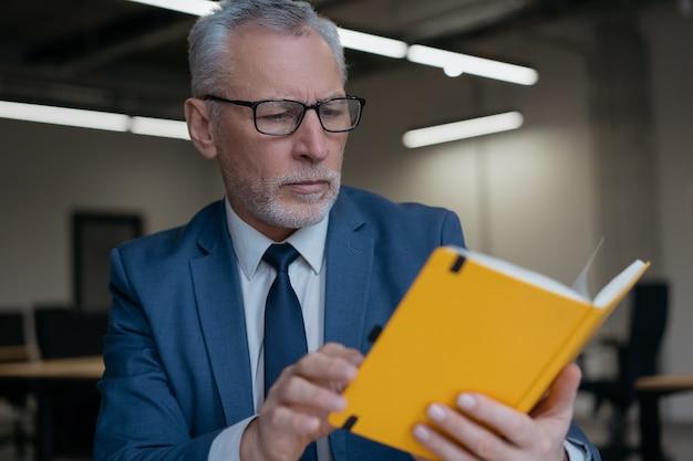 Przystojny starszy biznesmen noszenie okularów, czytanie książki, planowanie projektu, praca w biurze