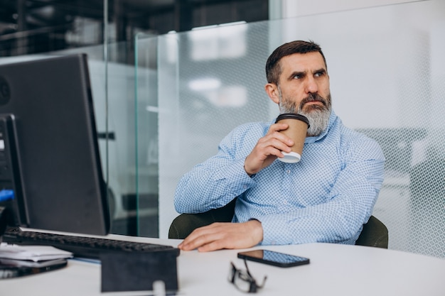 Przystojny starszy biznesmen pracujący na komputerze w biurze