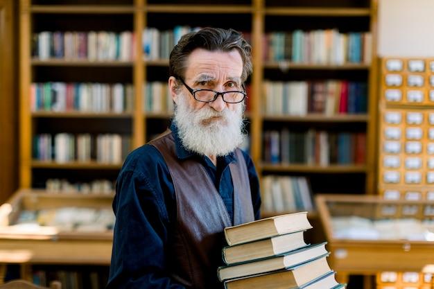Przystojny starszy brodaty emeryt, bibliotekarz lub nauczyciel, wybierając książki w bibliotece, trzymając stos książek, patrząc na kamery, półki na książki w tle