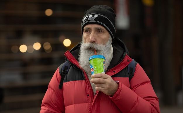 Przystojny starszy brodaty mężczyzna z papierową filiżanką porannej kawy odprowadzenie na ulicie.