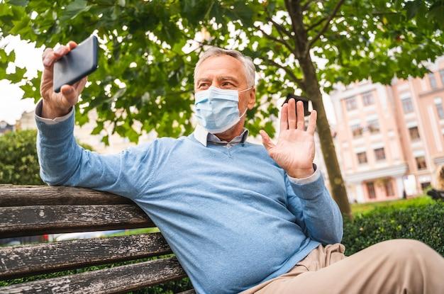 Przystojny starszy dorosły z maską w parku podczas kwarantanny pandemicznej koronawirusa
