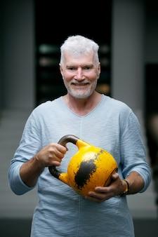 Przystojny starszy mężczyzna o siwych włosach z wagą kettlebell