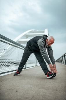 Przystojny starszy mężczyzna rozciąganie i rozgrzewka przed joggingu ćwiczenia wieczorem.