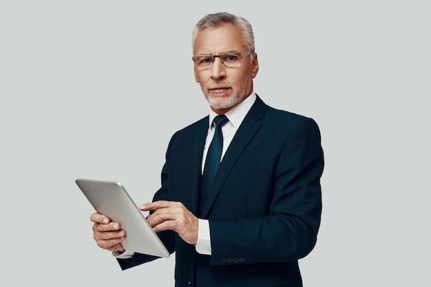 Przystojny starszy mężczyzna w pełnym garniturze, korzystający z cyfrowego tabletu i patrzący w kamerę, stojąc na szarym tle