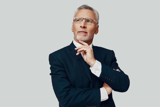 Przystojny starszy mężczyzna w pełnym garniturze odwracający wzrok i trzymający rękę na brodzie, stojąc na szarym tle