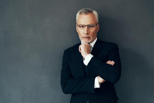 Przystojny starszy mężczyzna w pełnym garniturze, patrzący w kamerę i trzymający rękę na brodzie, stojąc na szarym tle