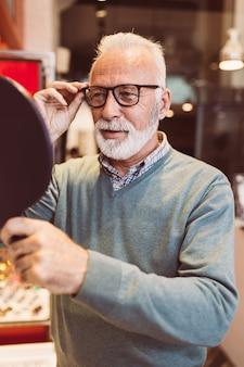 Przystojny starszy mężczyzna wybierając oprawki okularów w sklepie optycznym.