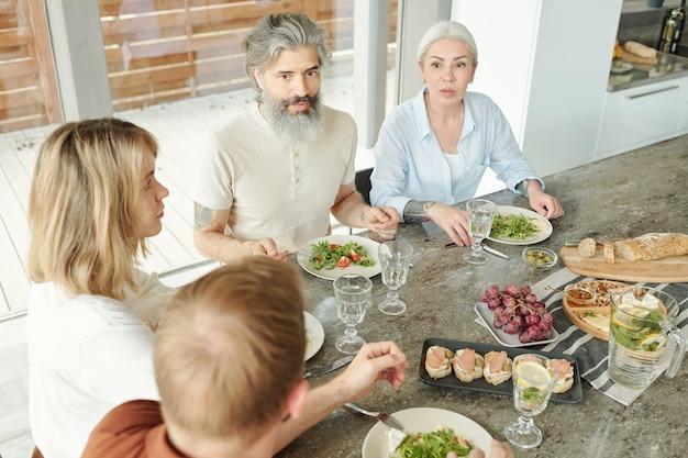 Przystojny starszy mężczyzna z wąsem i brodą siedzi przy stole i je sałatkę podczas rozmowy z gośćmi na kolację