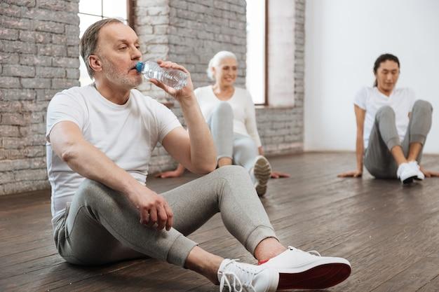 Przystojny starzec siedzi na podłodze, trzymając ręce na kolanach, trzymając butelkę w lewej ręce