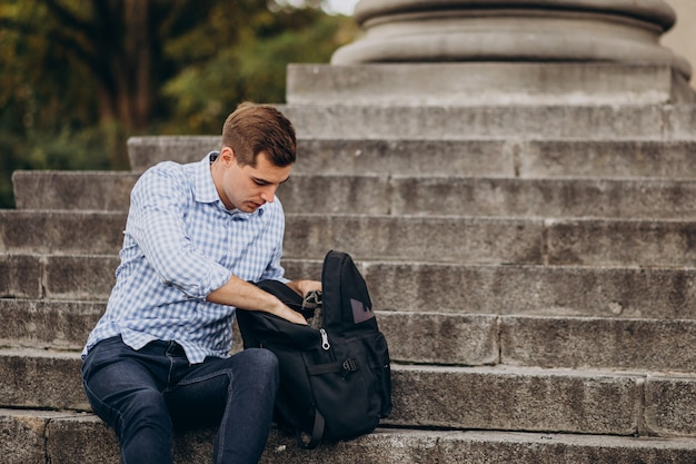 Przystojny student siedzi na schodach uniwersytetu i studiuje