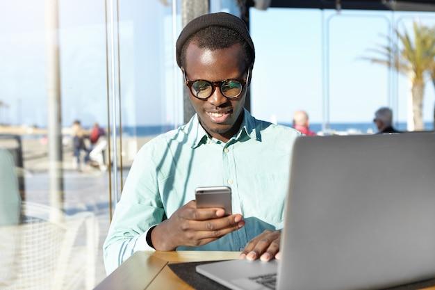 Przystojny student ubrany w stylowe akcesoria wpisując wiadomość na telefon komórkowy