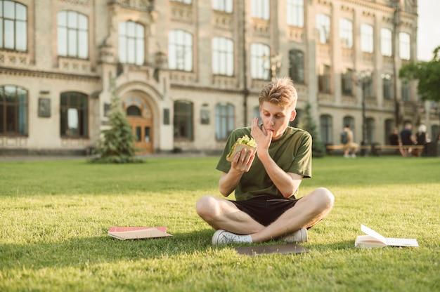 Przystojny student uniwersytetu je apetyczną kanapkę