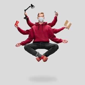 Przystojny student, wieloręki mężczyzna lewitujący na białym tle na szarym tle studio ze sprzętem. pojęcie zawodu, pracy, pracy, edukacji, rozwoju. wielozadaniowość jak shiva.