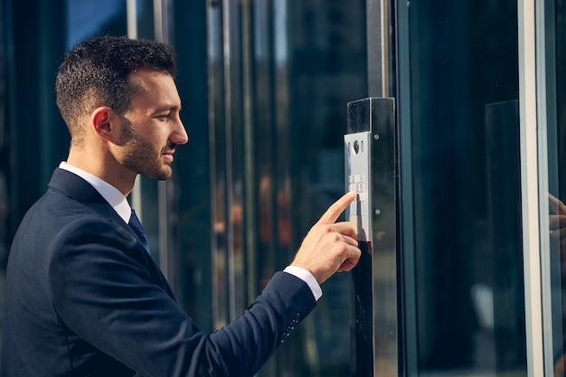 Przystojny stylowy biznesmen przebywający na zewnątrz w formalnych ubraniach, naciskając przycisk na budynku palcem