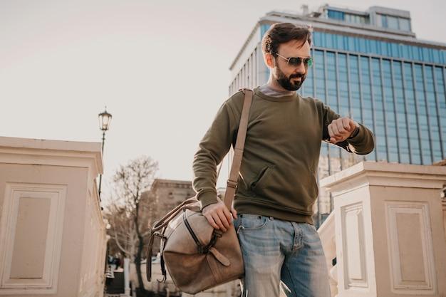 Przystojny stylowy brodaty mężczyzna spacerujący ulicą miasta ze skórzaną torbą podróżną w bluzie i okularach przeciwsłonecznych, trend w stylu miejskim, słoneczny dzień, patrząc na zegarek