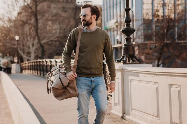 Przystojny stylowy brodaty mężczyzna spacerujący ulicą miasta ze skórzaną torbą podróżną w bluzie i okularach przeciwsłonecznych, trend w stylu miejskim, słoneczny dzień, pewny siebie i uśmiechnięty