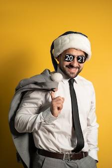 Przystojny stylowy brodaty uśmiechnięty mężczyzna santa na sobie niebieskie okulary przeciwsłoneczne kapelusz świętego mikołaja i garnitur, patrząc