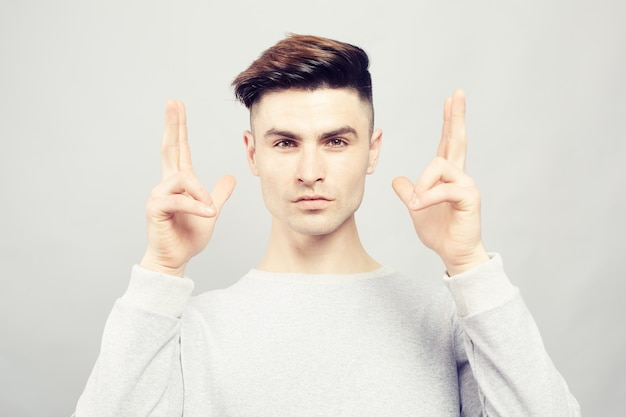 Przystojny stylowy facet pokazuje rozmiar gest
