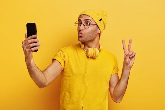 Przystojny stylowy hipster robi selfie, robi gest pokoju, ma złożone usta, trzyma smartfona