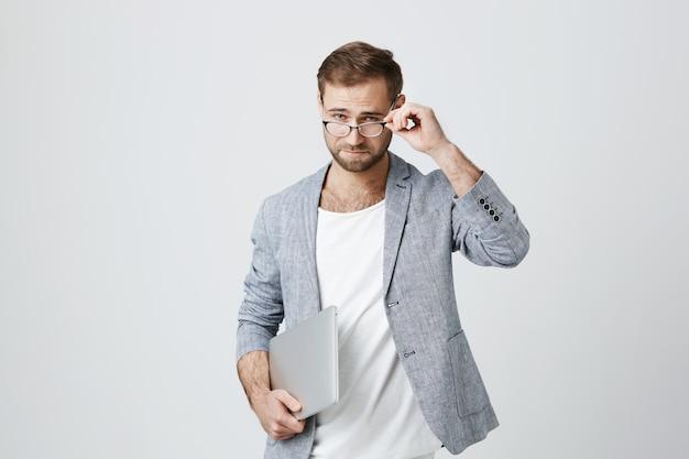 Przystojny stylowy męski przedsiębiorca w okularach z laptopem